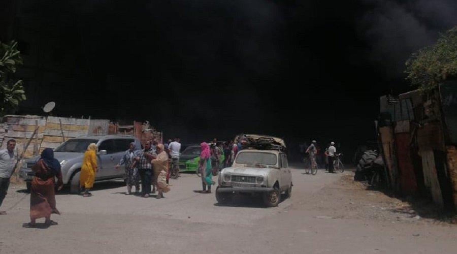 مواطنون بسيدي سليمان يحاولون إنقاذ بيوتهم الصفيحية من الحريق بعدما عجزت الوقاية المدنية عن إخماده